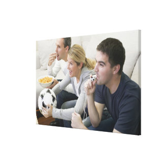 Friends watching TV with whistle, football and Canvas Print