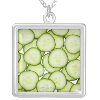 Full frame of sliced cucumber, on white silver plated necklace