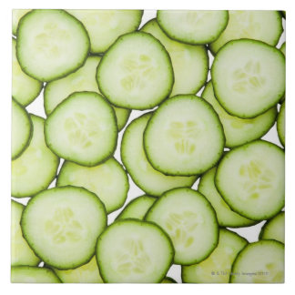 Full frame of sliced cucumber, on white tile