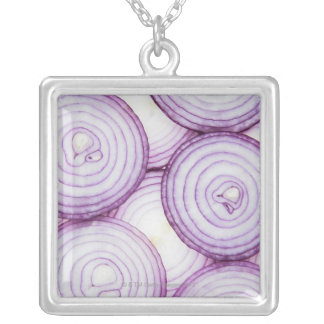 Full frame of sliced red onion, on white silver plated necklace