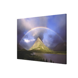 Full rainbow and stormy sky over Grinnell Canvas Print