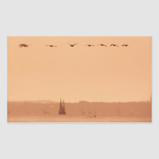 Geese flying passed a yacht in the morning rectangular sticker