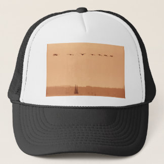 Geese flying passed a yacht in the morning trucker hat
