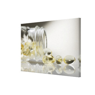 Gelcaps spilling out of glass bottle canvas print