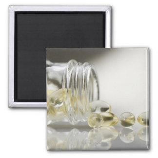 Gelcaps spilling out of glass bottle fridge magnet