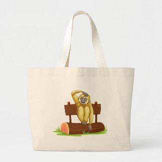 Gibbon sitting on log tote bags
