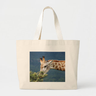 Giraffe eating some leaves large tote bag