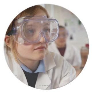 Girl (9-12) wearing protective goggles in plate