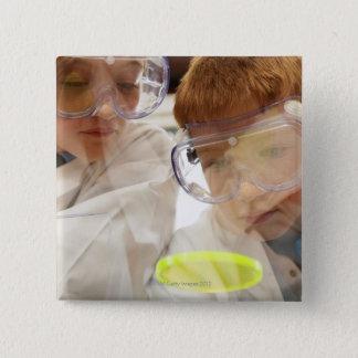 Girl and boy (11-13) looking at petri dish, view 15 cm square badge