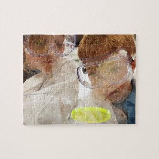 Girl and boy (11-13) looking at petri dish, view jigsaw puzzle