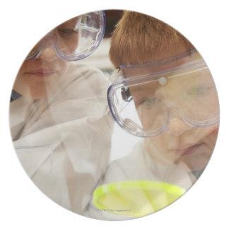 Girl and boy (11-13) looking at petri dish, view plate