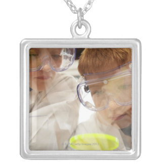 Girl and boy (11-13) looking at petri dish, view silver plated necklace