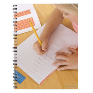 Girl doing homework notebooks
