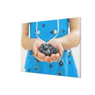 Girl holding fresh blueberries canvas print