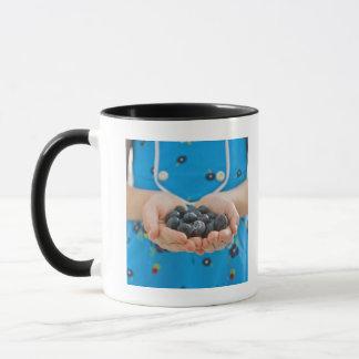 Girl holding fresh blueberries mug