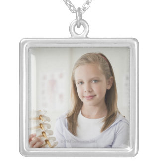 Girl holding model of spine in doctors office silver plated necklace