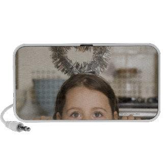 Girl in angel costume peeking from behind travelling speaker
