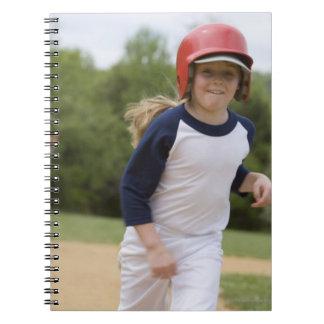 Girl in batting helmet running bases notebooks