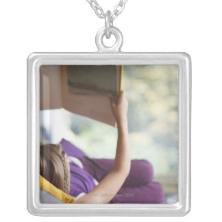 Girl laying down reading book silver plated necklace