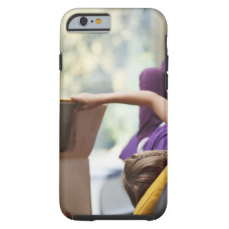 Girl laying down reading book tough iPhone 6 case