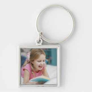 Girl laying in bed reading book key ring