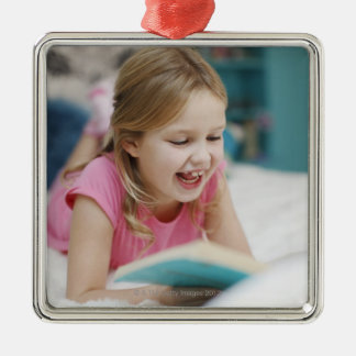Girl laying in bed reading book Silver-Colored square decoration