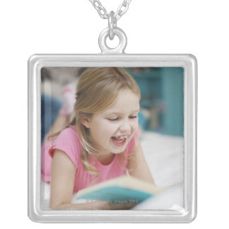 Girl laying in bed reading book silver plated necklace