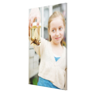 Girl looking at insect in jar in classroom canvas print