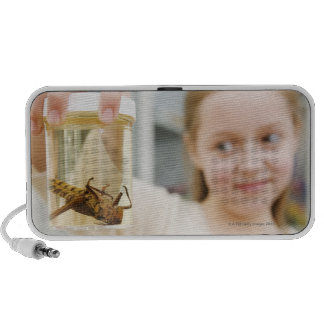 Girl looking at insect in jar in classroom iPod speakers