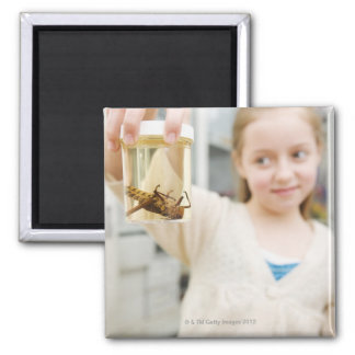 Girl looking at insect in jar in classroom magnet