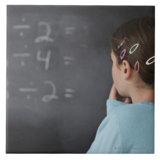 Girl looking at math equations on blackboard large square tile