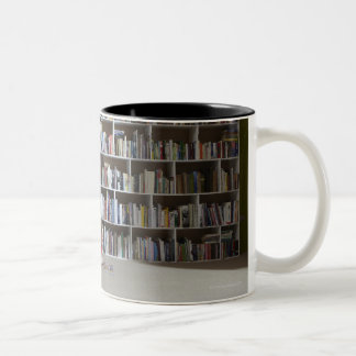 Girl reading by bookshelves Two-Tone coffee mug