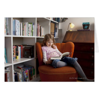 Girl reading by the bookshelf greeting card
