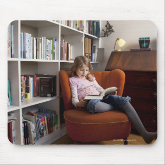 Girl reading by the bookshelf mouse pad