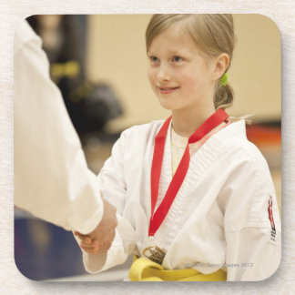 Girl receiving a medal at a Karate championship Coaster