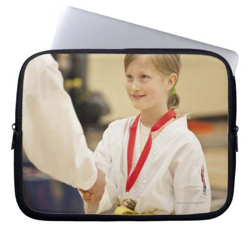 Girl receiving a medal at a Karate championship Laptop Sleeves