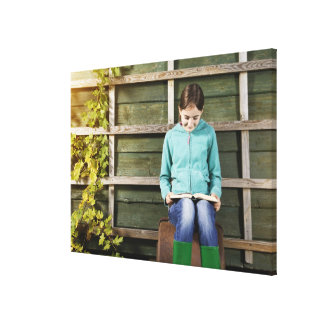 Girl sitting and reading book near vine canvas print