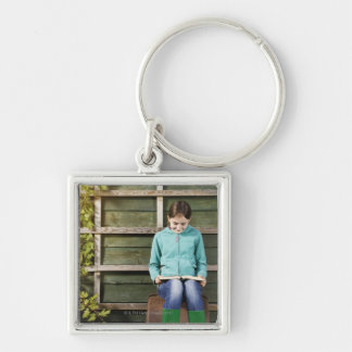 Girl sitting and reading book near vine key ring