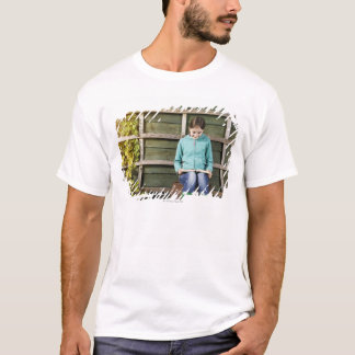Girl sitting and reading book near vine T-Shirt