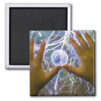 Girls hands on a plasma ball magnet