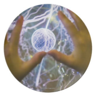 Girls hands on a plasma ball plate