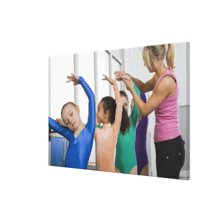 Girls stretching in gymnastics class stretched canvas prints