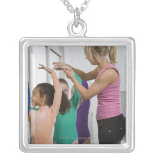 Girls stretching in gymnastics class silver plated necklace