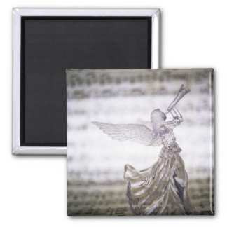 Glass angel playing trumpet and image of sheet magnet