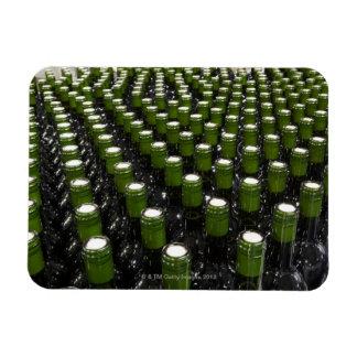 Glass wine bottles in a wine bottling factory. magnet