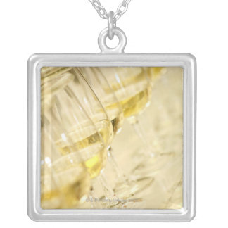 Glasses of white wine for wine tasting close up personalized necklace