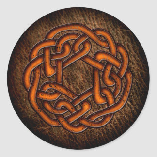 Glowing orange celtic ornament on leather classic round sticker