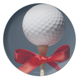Gold ball on tee with red bow dinner plates