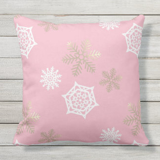 golden and white snowflakes against pale pink cushion