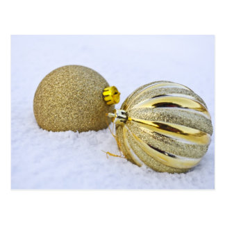 Golden Christmas baubles in snow Postcards